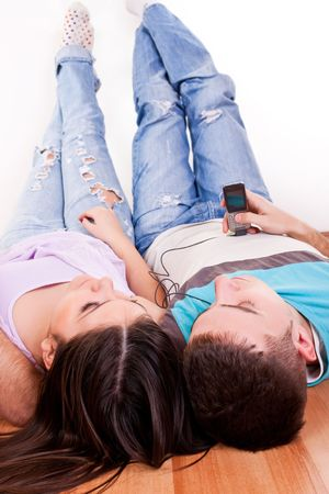 close-up of a happy young couple lying on the floor relaxing and listening music photo