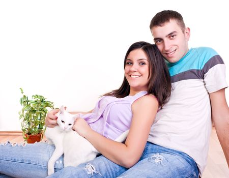 happy smiling young couple sitting on the floor with their pet cat photo