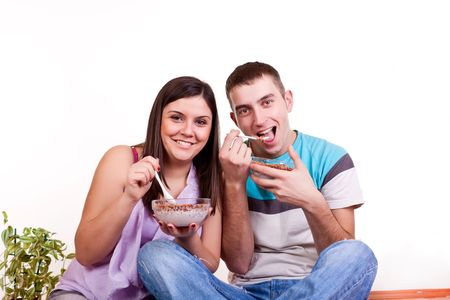 happy smiling young couple sitting on the floor and eating  photo