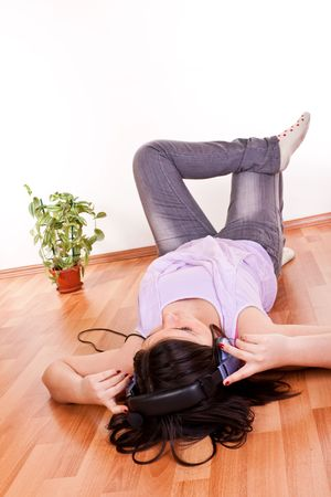 young brunette girl relaxing on the floor with earphones on her head photo