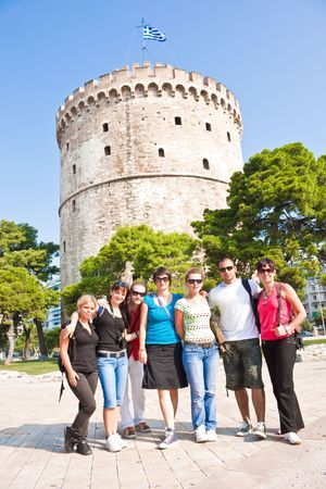 easygoing: happy young tourist in front of white tower in Greece Stock Photo