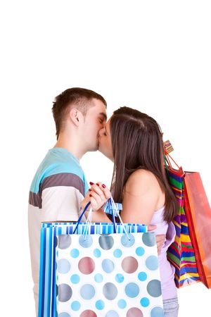 happy young couple kissing while holding colorful shopping paper bags Stock Photo - 6599721