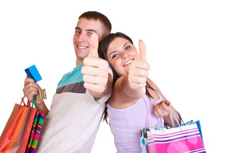 happy young couple holding bags satisfied with thumbs up photo