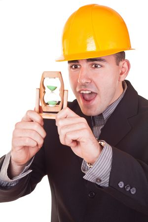 young businessman with helmet on his head holding hourglass and watching time photo