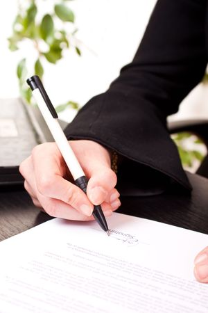 hand holding pen: close-up of a businesswomans hand holding pen and signing documents