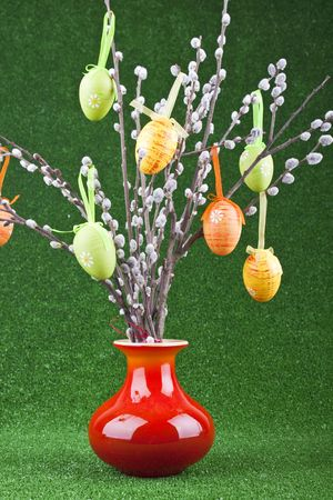 colorful easter tree in red vase on green background photo