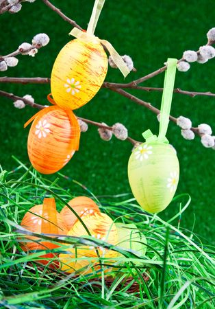 easter tree and nest with colorful eggs in grass photo