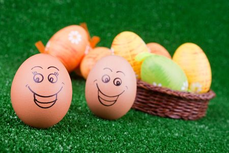 two smiling easter eggs on green grass photo