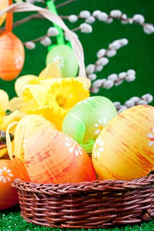close-up of easter eggs in nest and flowers photo