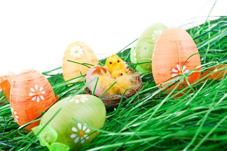 colorful easter eggs in grass and chicken in nest photo