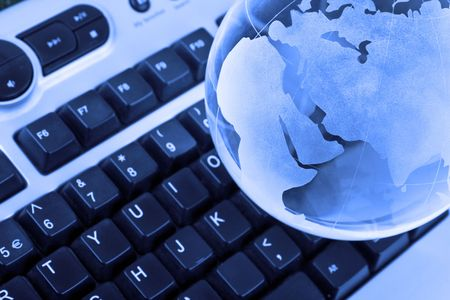 keyboard and glass earth globe - focus on globe