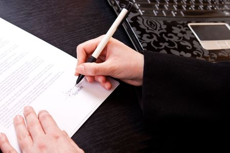 close-up of a womans hand holding pen and signing papers Stock Photo - 6667603
