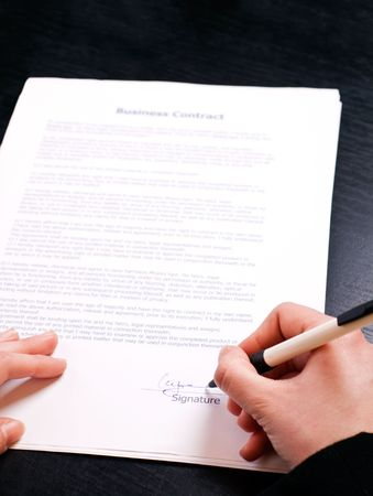 hand holding pen: womans hand holding pen and signing papers Stock Photo