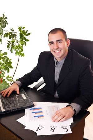 handsom: handsom young businessman sitting satisfied in his office with laptop