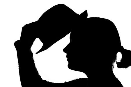 young woman putting hat on her head � silhouette photo