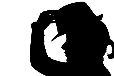 young girl putting hat on her head – silhouette photo
