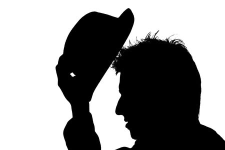 delineation: young man putting hat on his head � silhouette