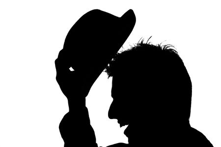 delineation: young male putting hat on her head � silhouette