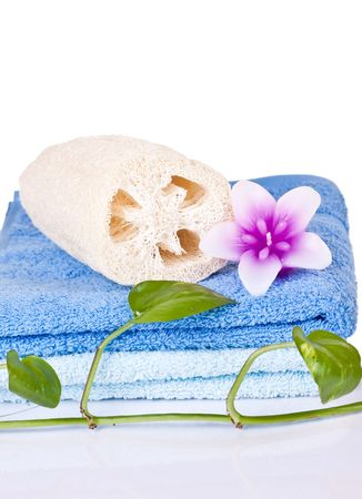 loofah and flower candle on blue towels decorated with plant photo