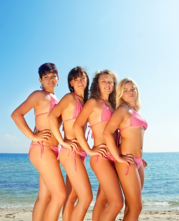sexy young girls: sexy young girls in pink bikinis on sunny beach Stock Photo
