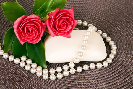 soap on brown mat decorated with red roses and pearls photo