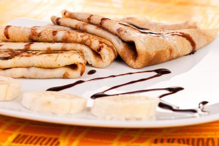 delicious pancakes on plate decorated with banana rings photo