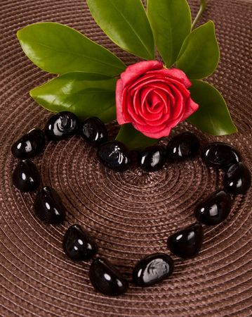 black stones in heart shape on mat decorated with rose and leaf Stock Photo - 6820291