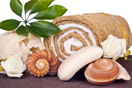 closeup of stones soap seashell loofah and towel on brown mat photo