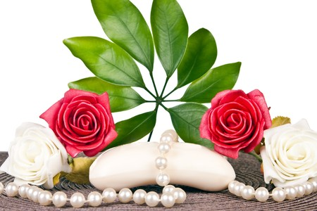 soap on brown mat with white and red roses and pearls photo