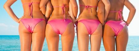 four girls in bikini from behind posing on beach