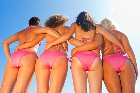 young girls bottom in pink bikini against the blue sky photo