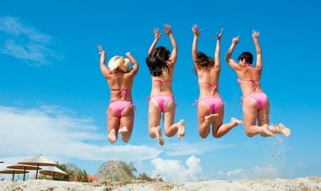 four girls in pink bikinis jumping on sandy beach