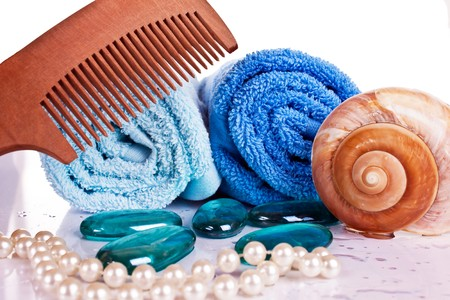 folded blue towels with comb on top and other accessories on the side photo