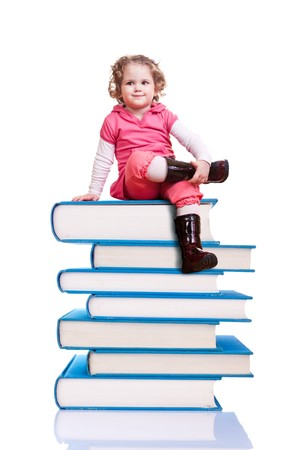 cute little girl sitting on a group of blue books photo