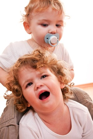 pacifier: little baby boy sitting on sisters back pulling her hair Stock Photo