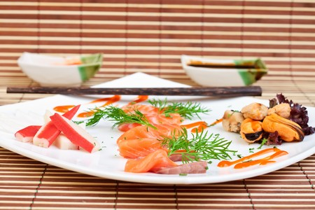 slices of delicious salmon decorated with sauce spices and seafood photo