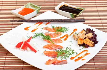 slices of delicious salmon decorated with  spices and seafood photo