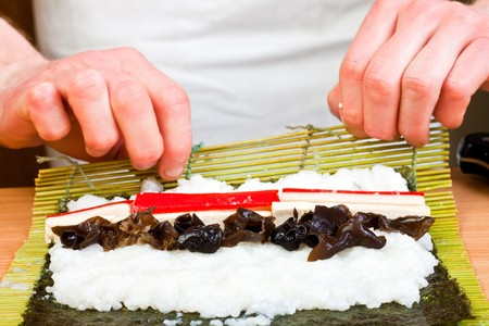 close-up of chefs hands preparing Japanese food - sushi photo