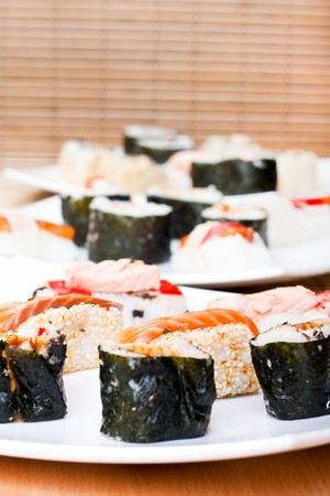 plates with sushi rolls decorated with salmon and tuna photo