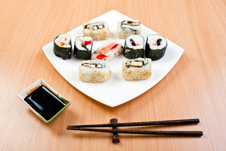 plate of delicious sushi on table with bowl of sauce and chopsticks photo