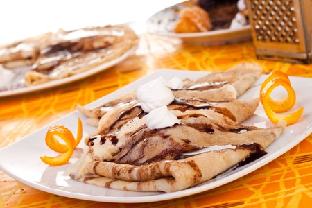plate of pancakes decorated with orange peel and whipped cream photo