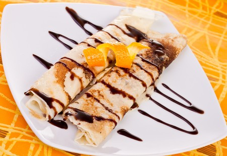 plate of rolled pancakes with orange and syrup on top photo