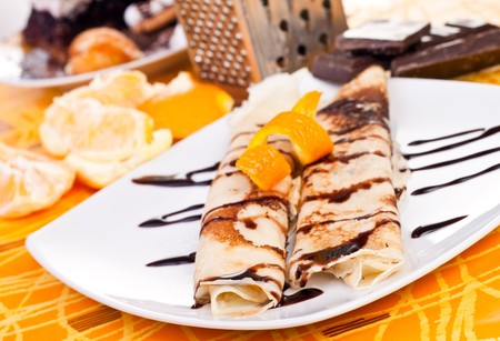 plate of filled pancakes decorated with orange peel photo
