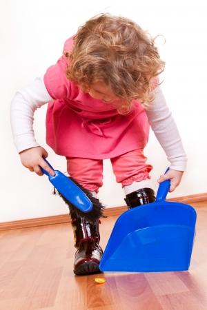 primer plano de una niña pequeña ordenada, sosteniendo la escoba y pista de pádel