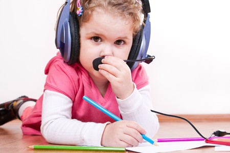little girl playing with headset and crayons on the floor  photo