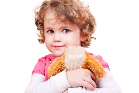 pretty little blond girl hugging toy dog   photo