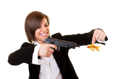 young attractive dangerous woman aiming at gold fish photo