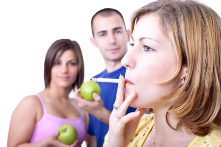 women smoking: young woman smoking cigar while friends eating apple