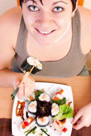 young woman eating sushi roll with chopsticks photo