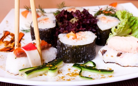 close-up of hand holding sushi roll with chopsticks and dipping photo